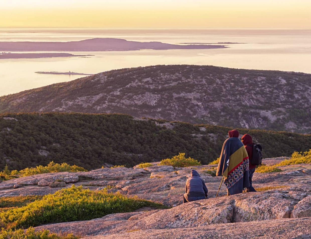A group of people watch the sunrise from a vista at Acadia National Park