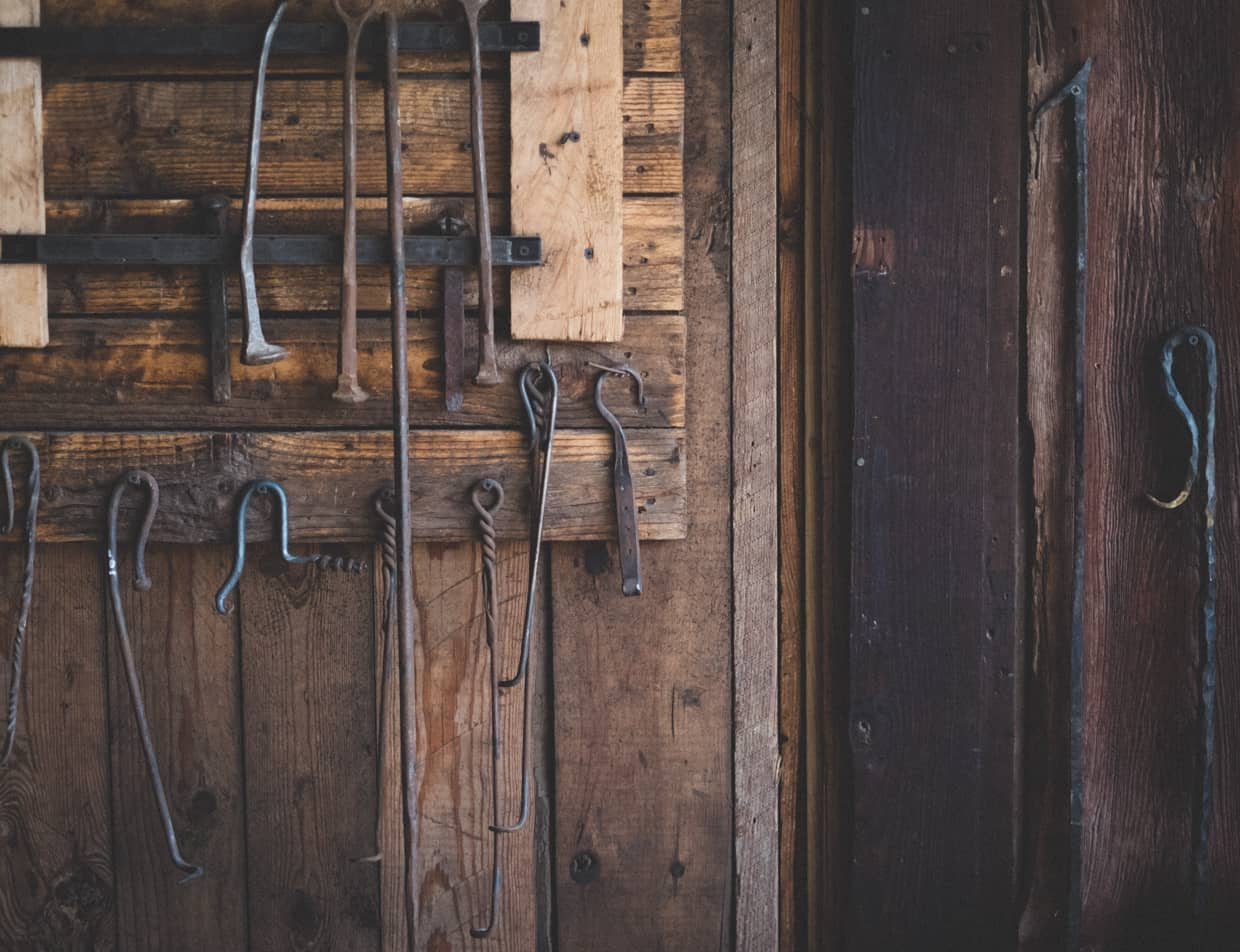 Wooden wall with blacksmith tools hanging from hooks