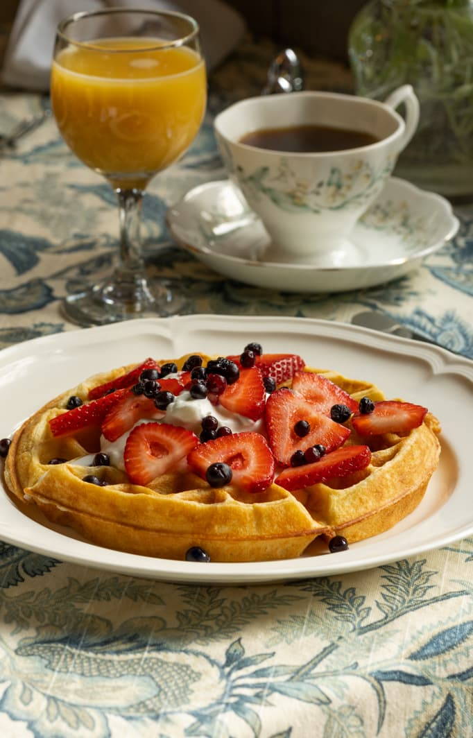 Delicious breakfast of waffles served with coffee and orange juice