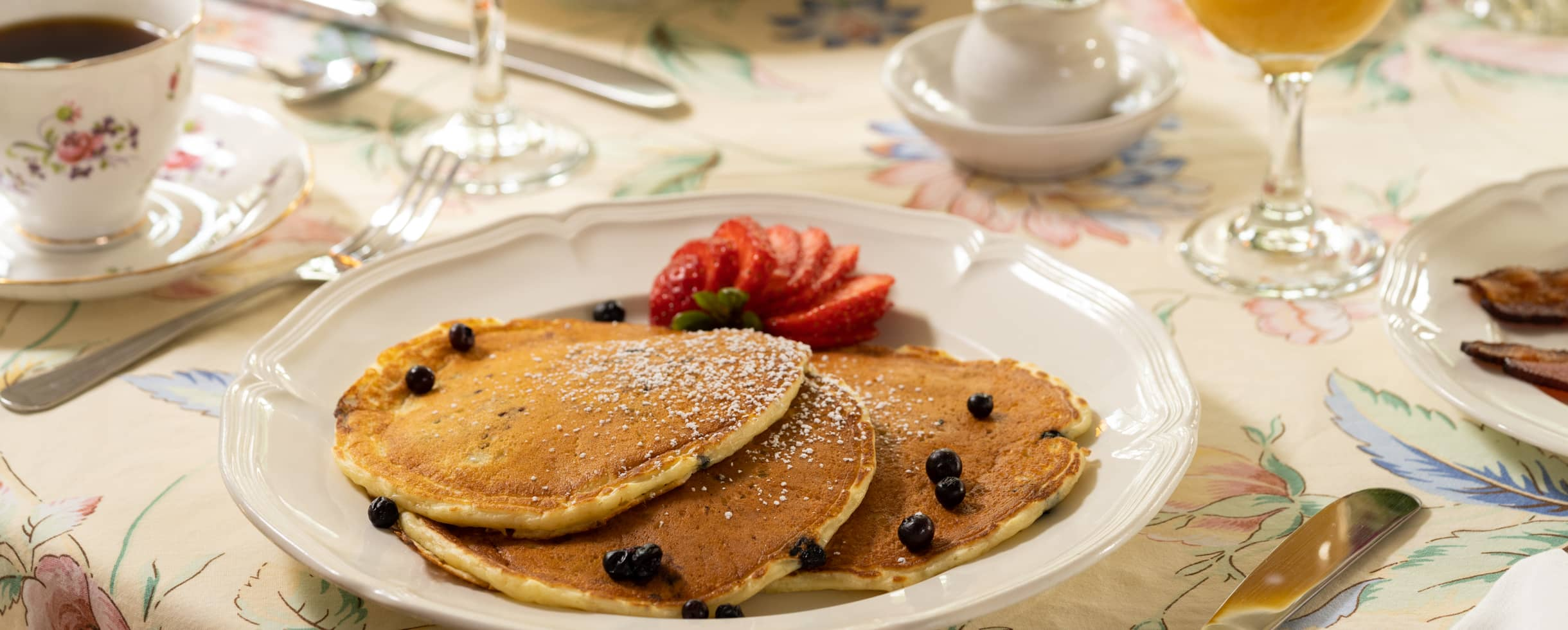 blueberry pancakes served with fresh cut strawberries
