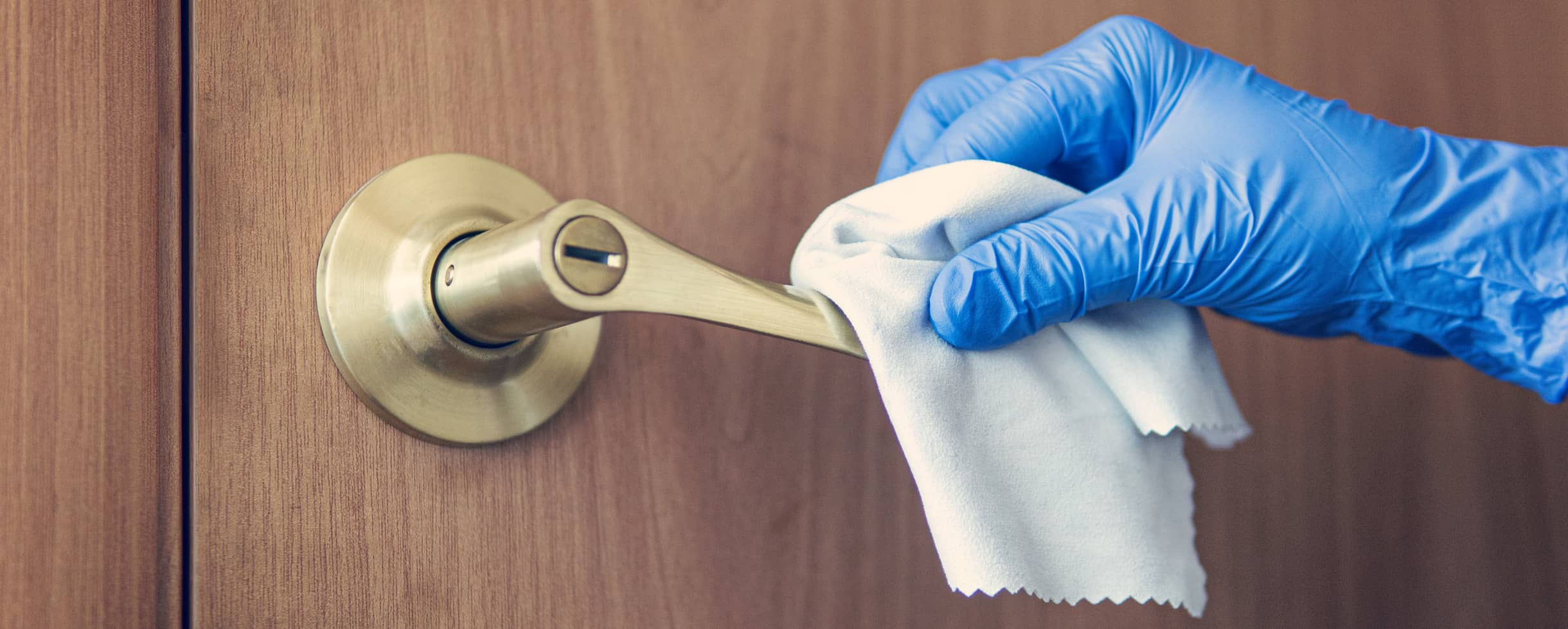 Person wearing a rubber glove disinfecting a door handle