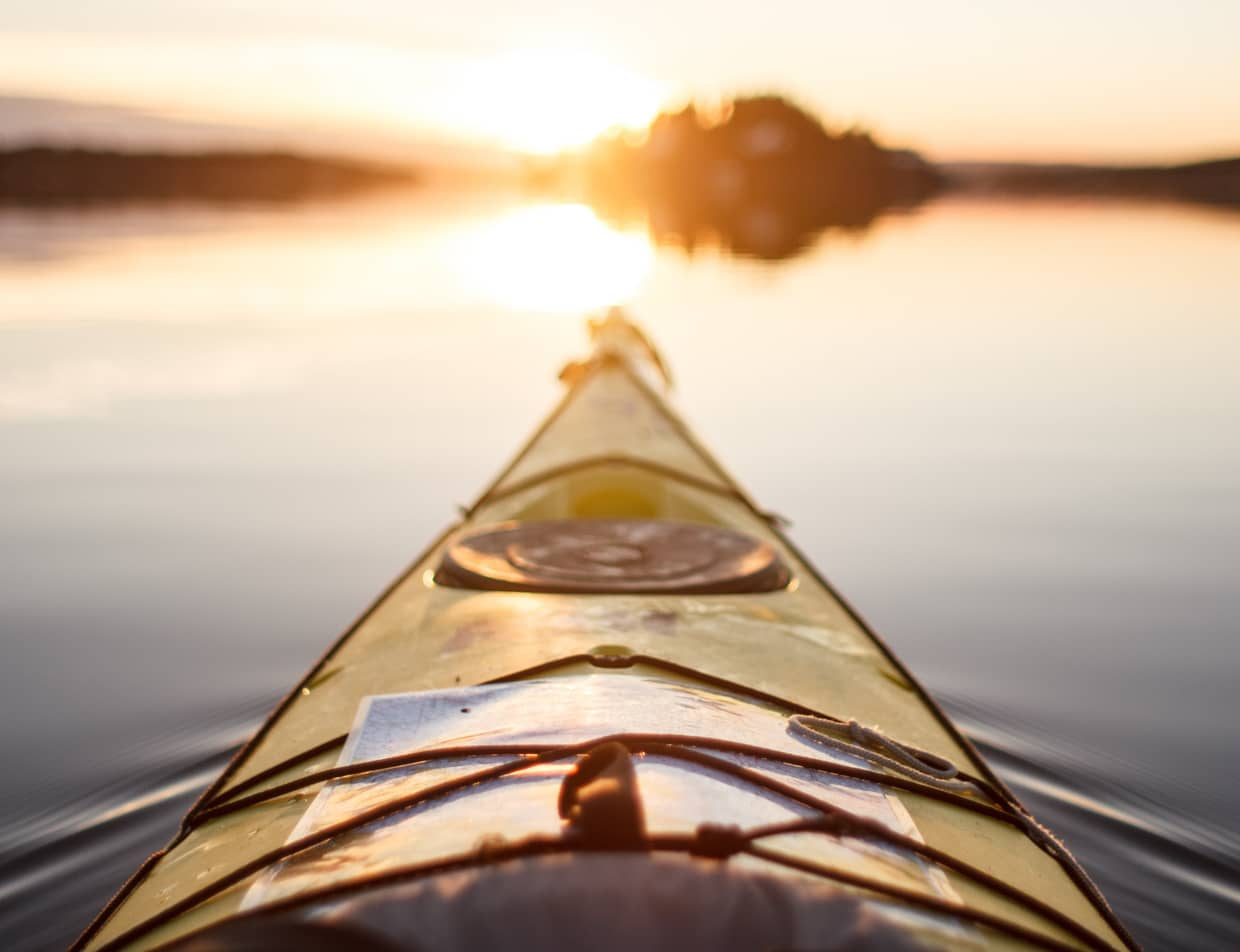 Kayak pointing to the sun on a calm body of water