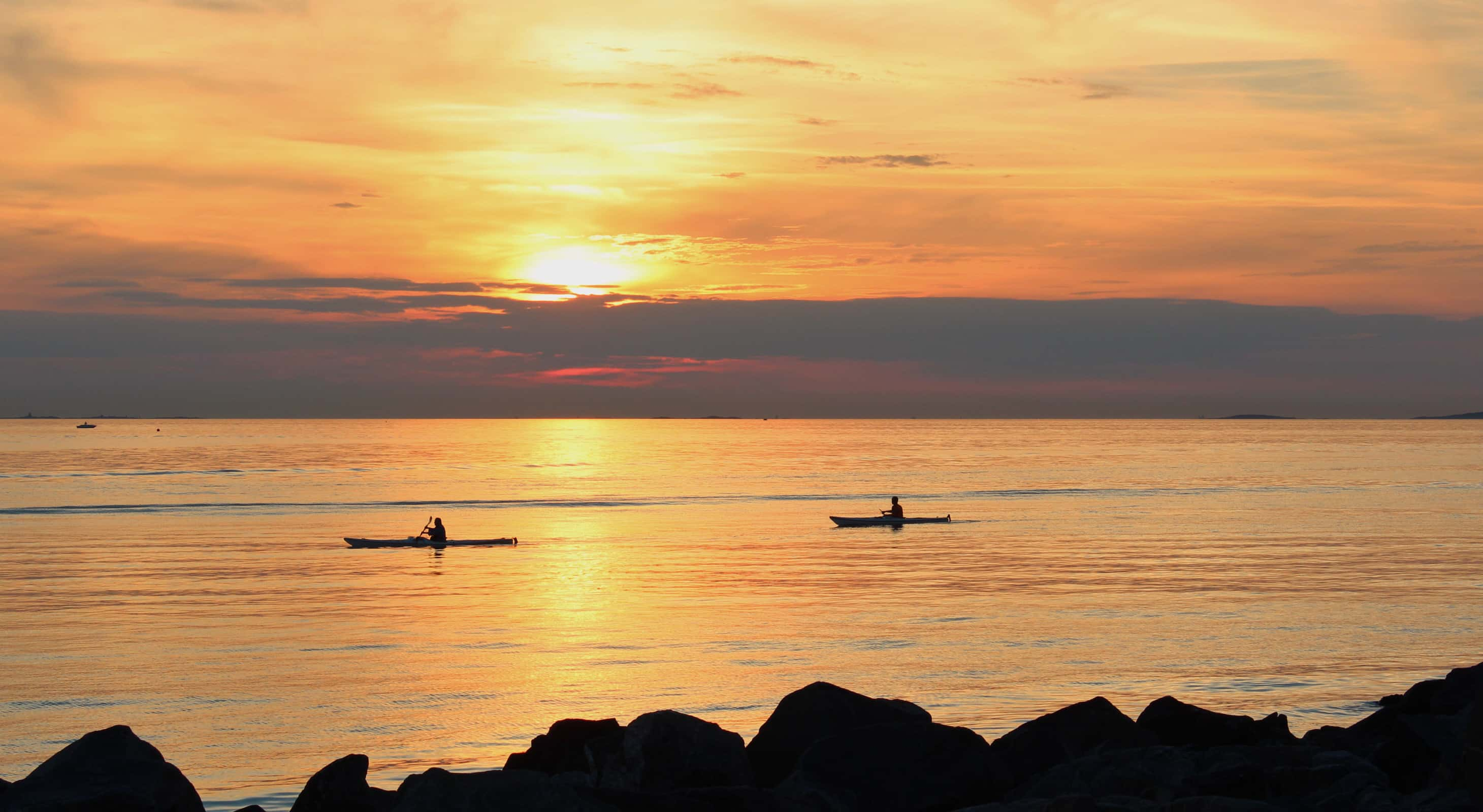 Two kayakers in the ocean at sunrise