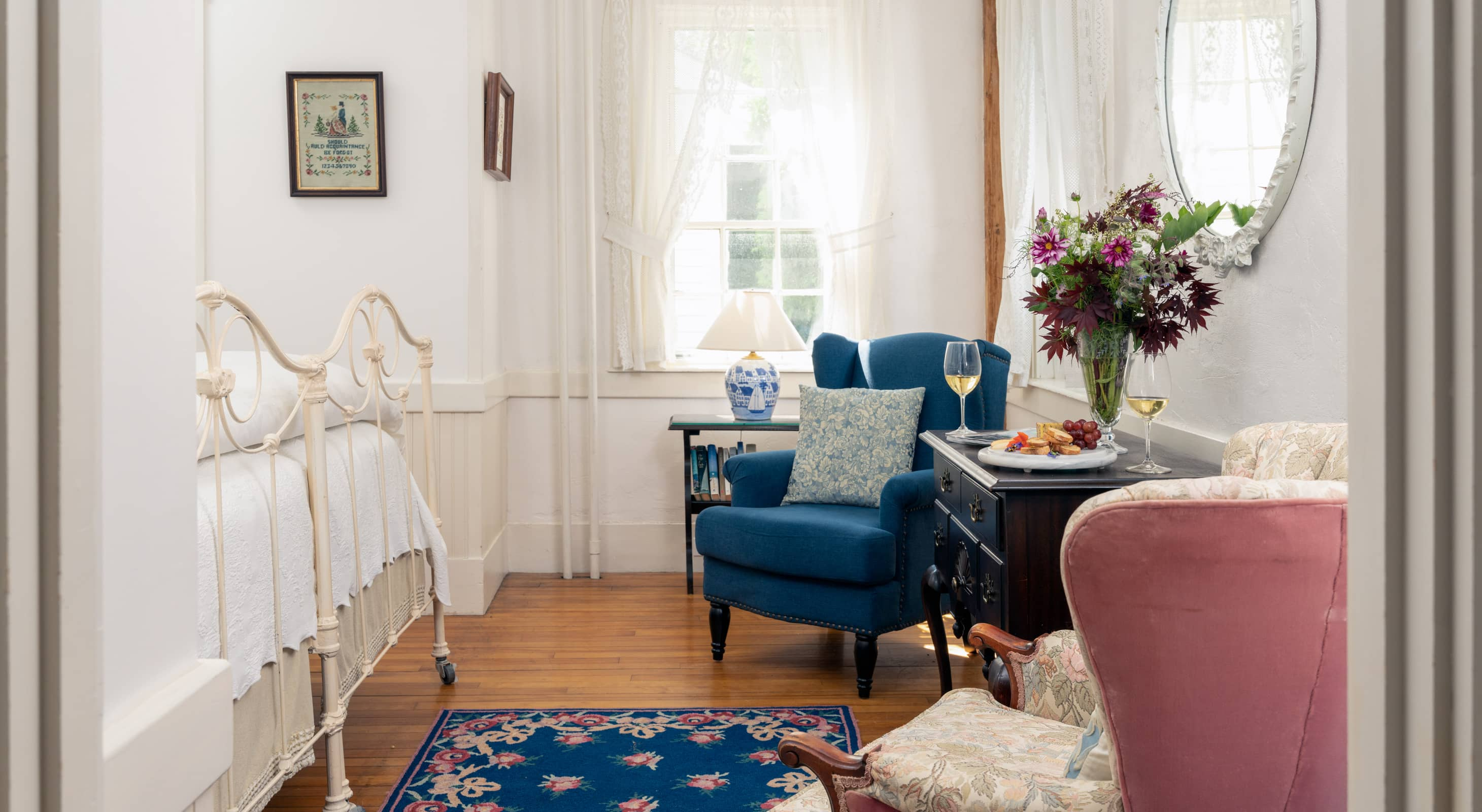 Room 1 with hardwood floors a blue area rug and a seating area for two