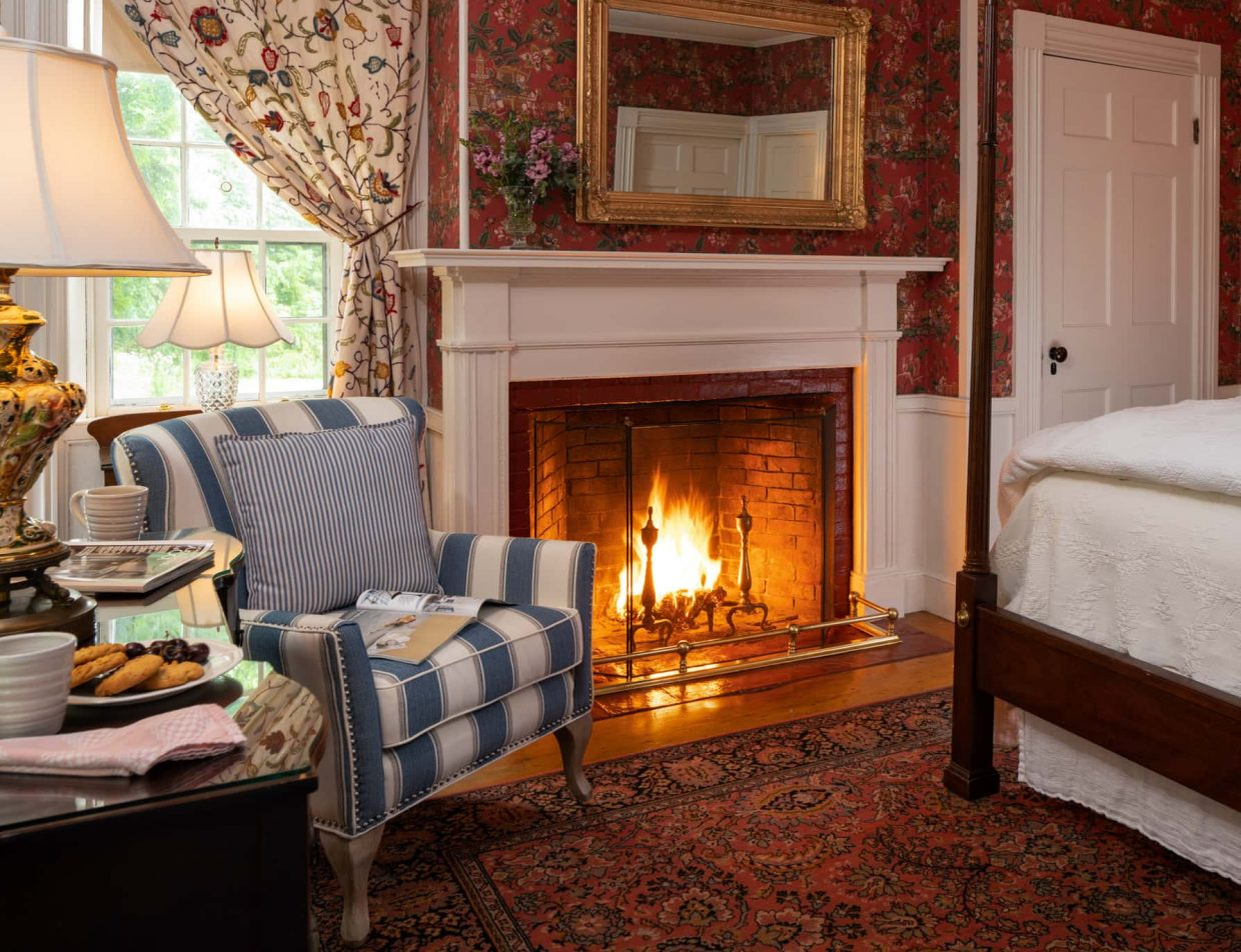 Room 10 with a king-size bed and a fireplace with a large area rug and seating area for two