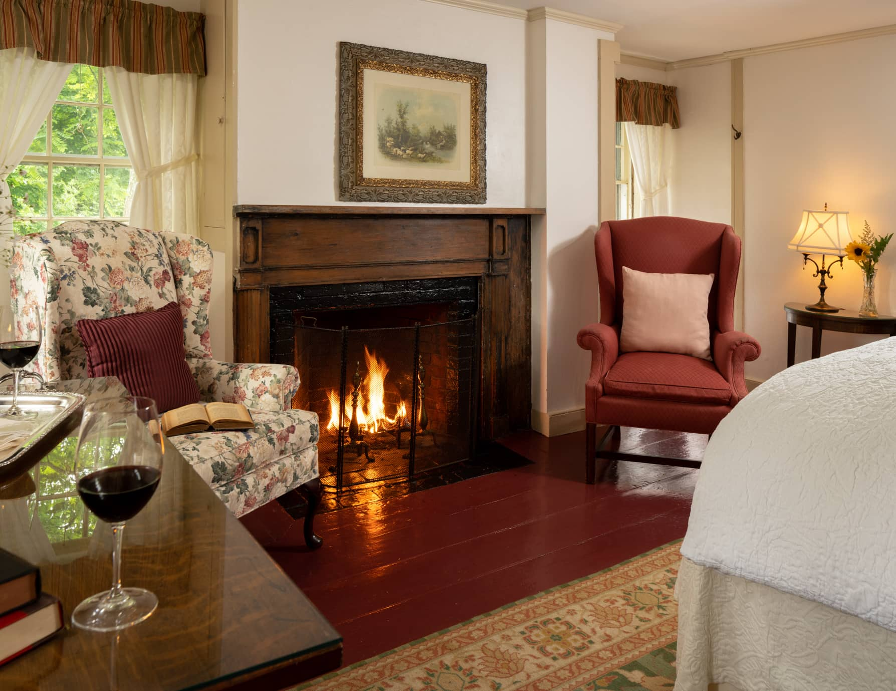 Room 5 with a king bed a seating area and fireplace and hardwood floors with a large area rug