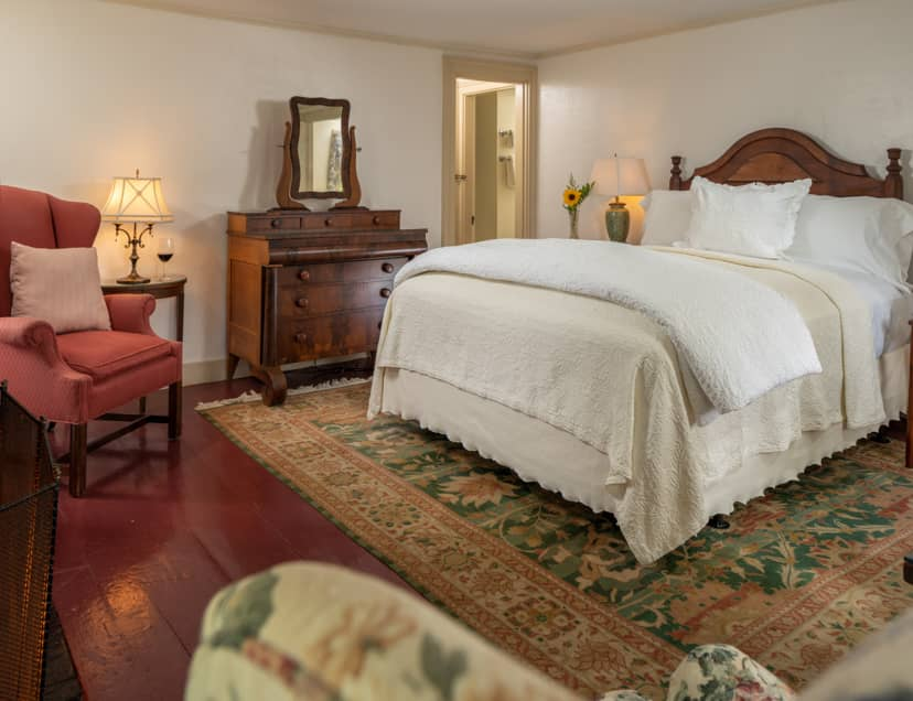 Room 5 with a queen bed hardwood floors with a large area rug and seating for two