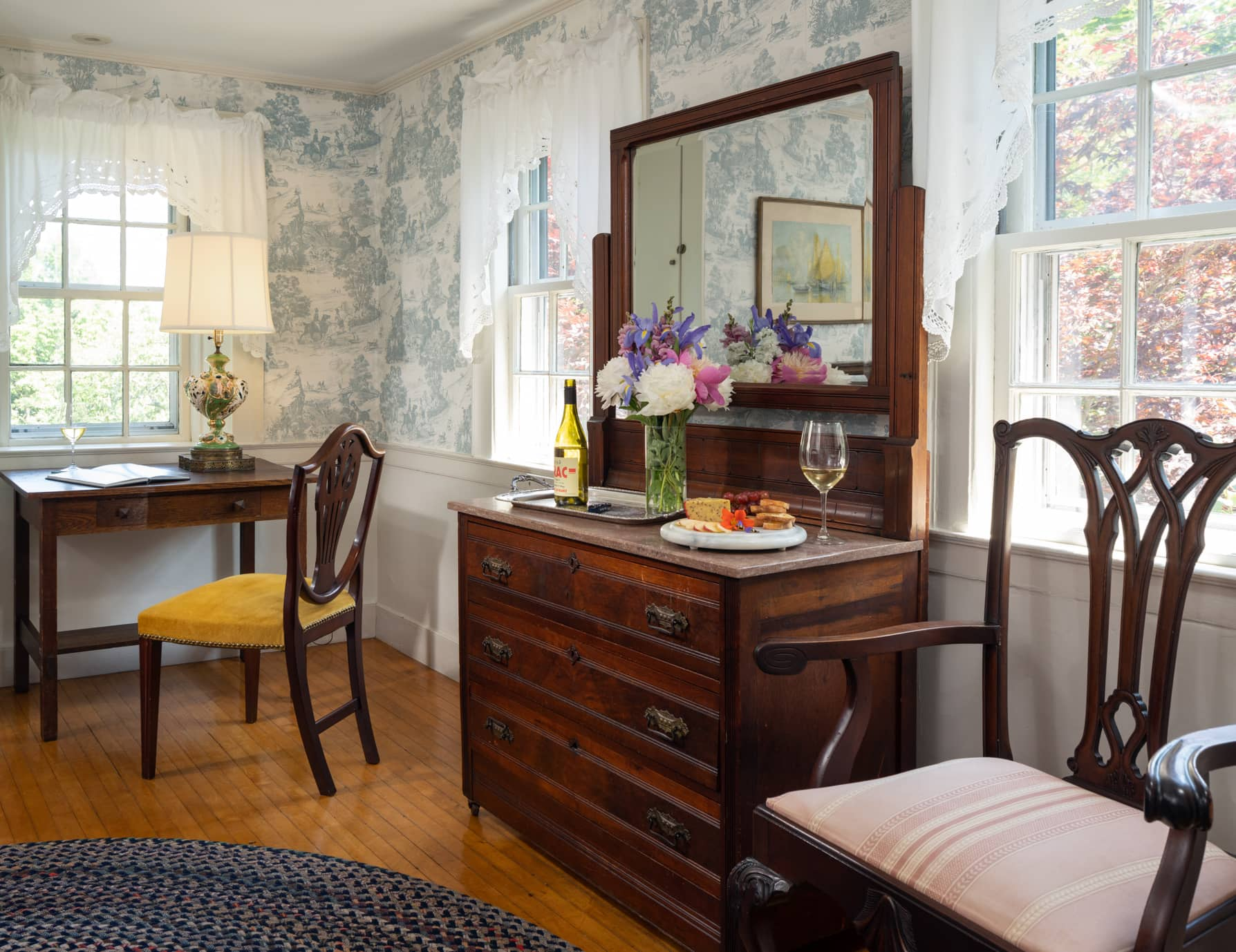 Room 6 writing desk and a cabinet with a mirror set against a wall with large windows