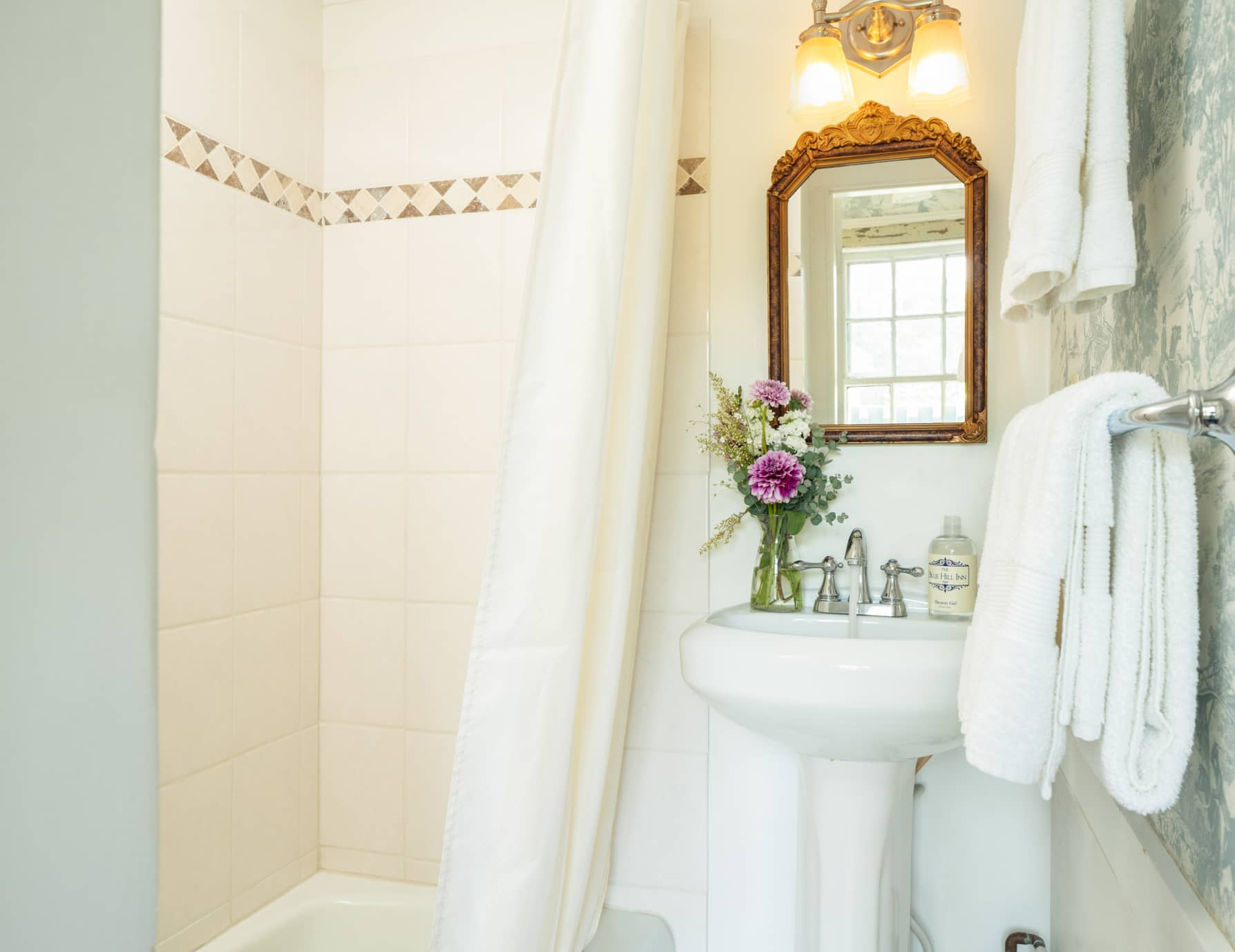 Room 6 bathroom with a small sink and mirror and a tub shower combination