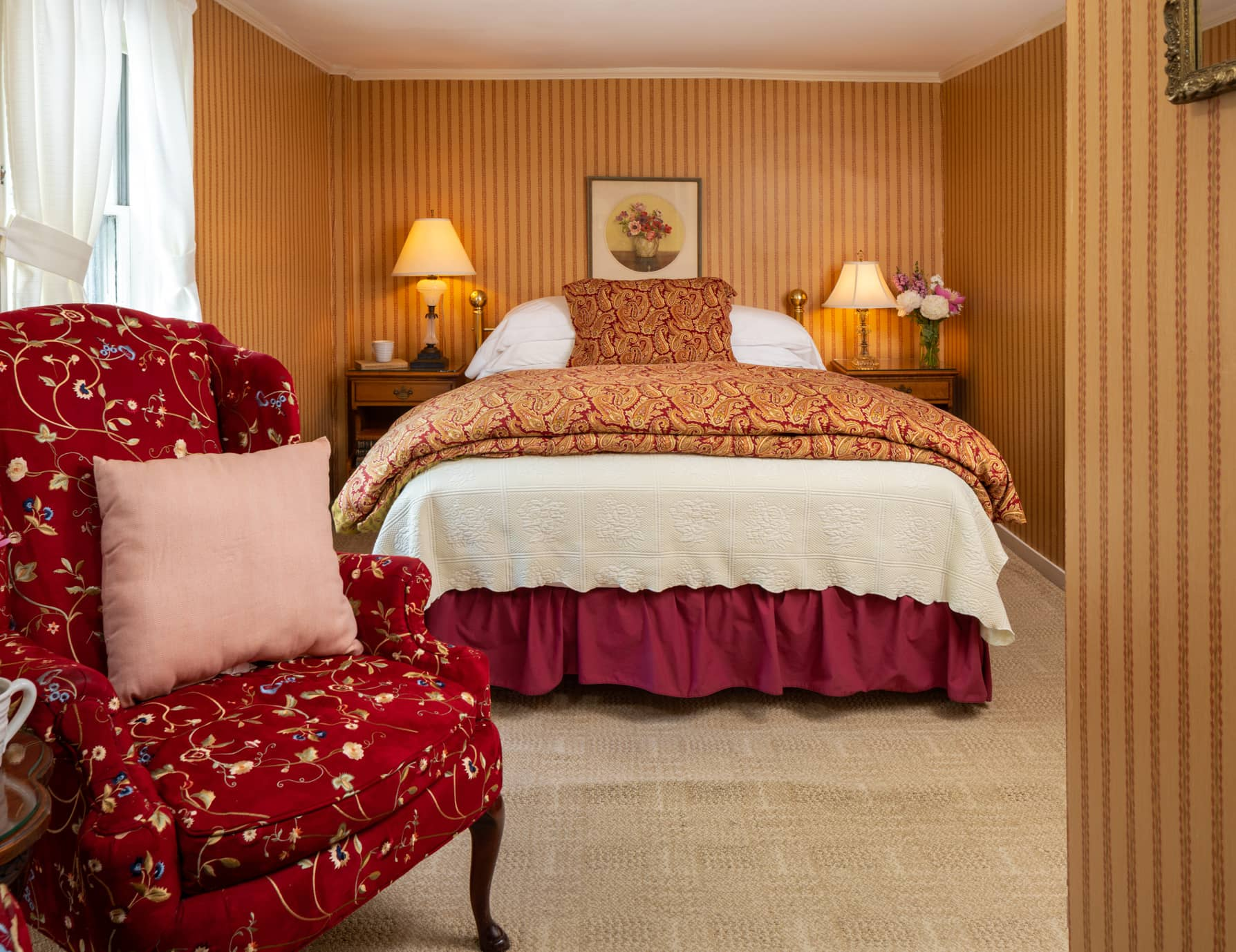 Room 7 with a queen bed carpet flooring and a red chair