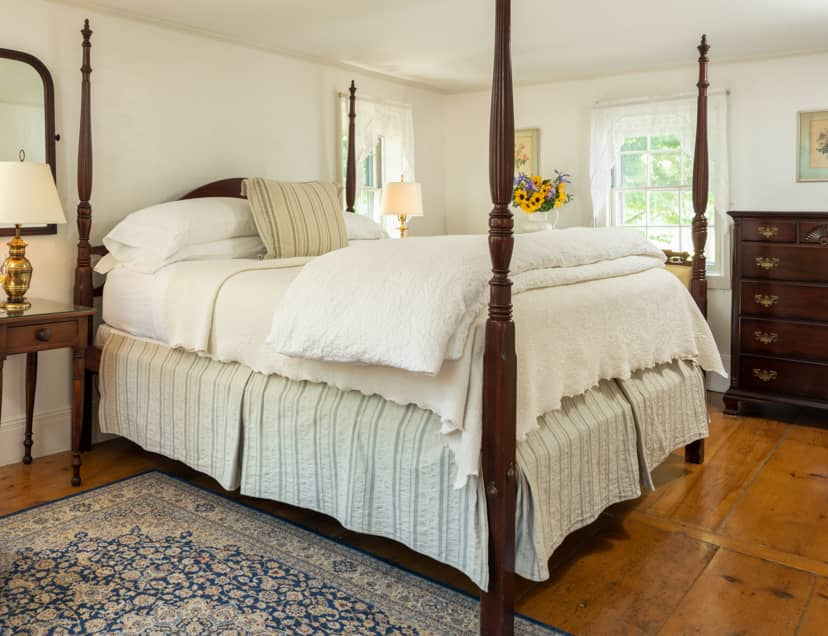 Room 8 with a four poster king bed hardwood floors and large windows