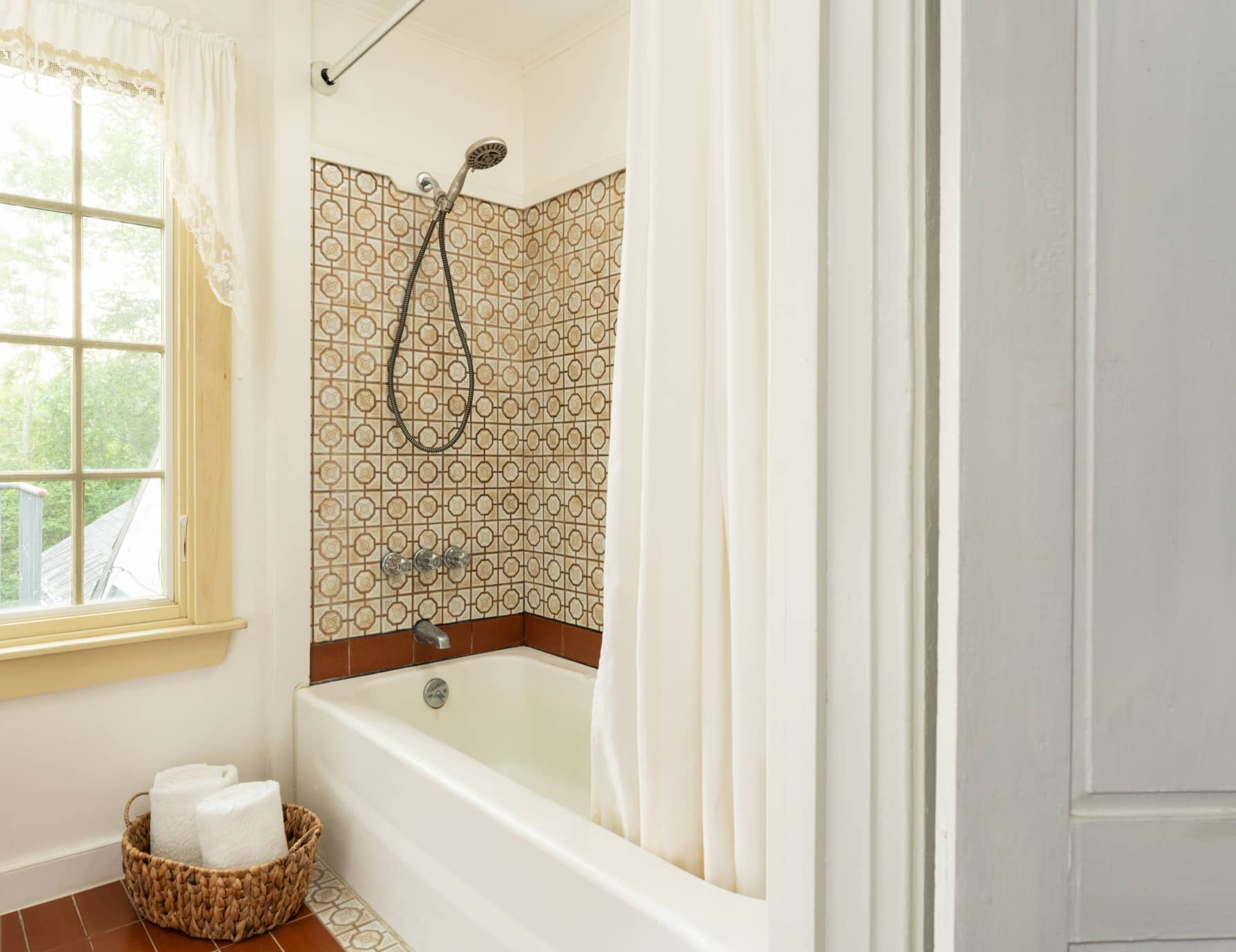 Room 9 bathroom with a large window and a shower tub combination